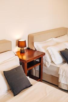 Dwa łóżka z biało-czarnymi poduszkami i drewnianym stołem z lampką nocną między nimi