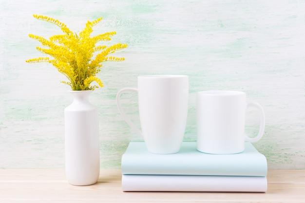 Dwa makiety białego kubka do kawy i cappuccino ze złotą trawą