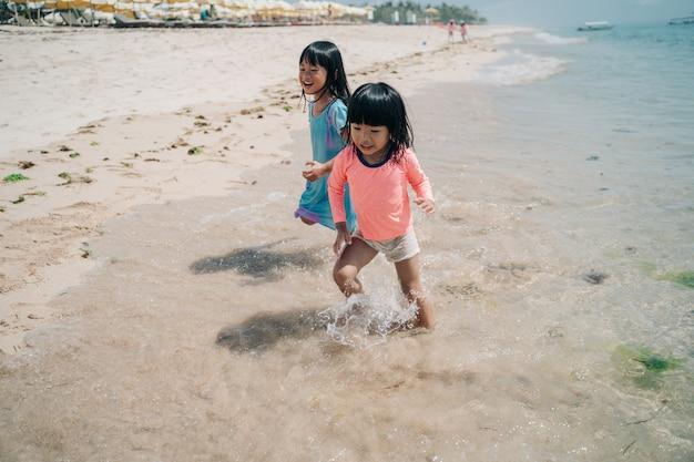 Dwa mała azjatycka dziewczyna biega unikać fal