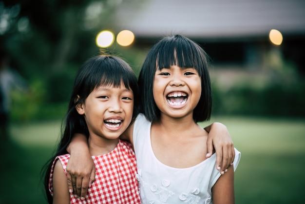 Dwa mała dziewczynka przyjaciela bawić się śmieszny w parku