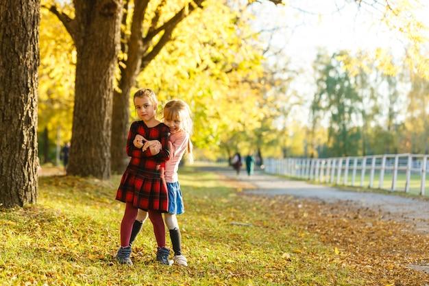 Dwa mała dziewczynka przyjaciół uczennica w parku.