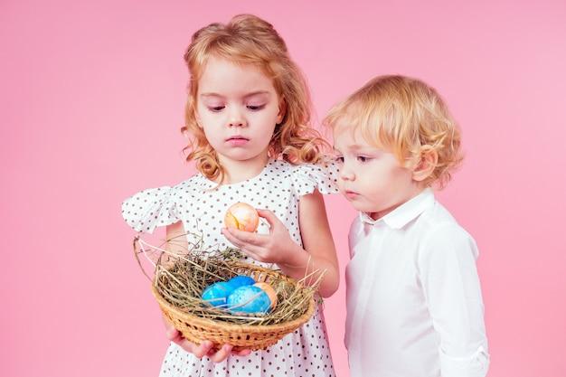 Dwa małe blond dziecko z pisklęciem kogut wielkanoc w studio różowym tle. piękny chłopiec i dziewczynka dzieci świętujące święta wielkanocne ze zwierzętami, malowane jajka w wiklinowym koszu. prezent urodzinowy marzeń