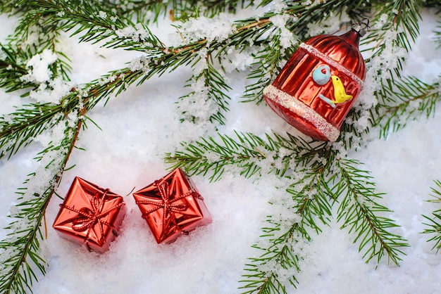 Dwa małe czerwone błyszczące pudełka z prezentami i zabawką bożonarodzeniową