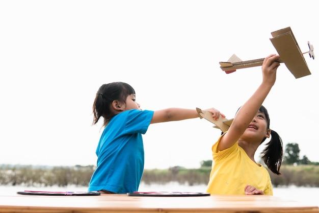 Dwa małe dzieci bawiące się tekturowym samolocikiem w parku w ciągu dnia.