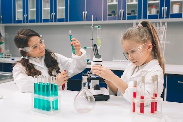 Dwa małe dzieci w fartuchu nauki chemii w szkolnym laboratorium. młodzi naukowcy w okularach ochronnych przeprowadzający eksperyment w laboratorium lub szafce chemicznej. badanie składników do eksperymentów.