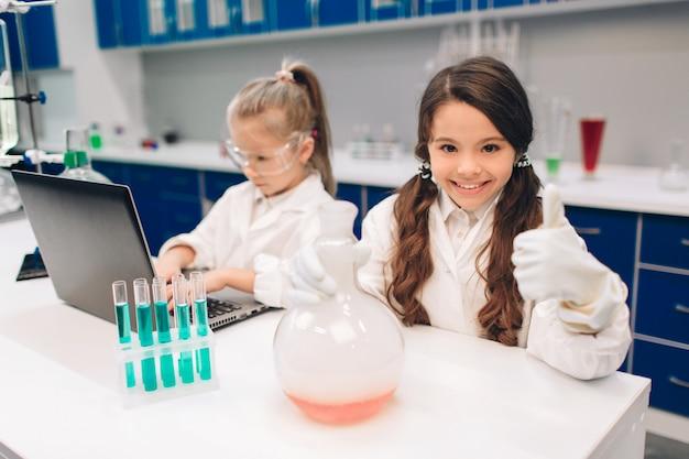 Dwa małe dzieci w fartuchu nauki chemii w szkolnym laboratorium. młodzi naukowcy w okularach ochronnych przeprowadzający eksperyment w laboratorium lub szafce chemicznej. kciuki w górę