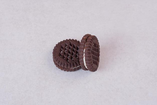 Dwa, małe, słodkie ciasteczka czekoladowe na białym stole.