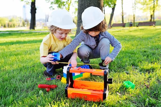 Dwa małe słodkie dzieci w kaskach budowlanych bawią się w robotnikach lub budowniczych zabawkowymi narzędziami w parku na trawie.