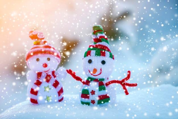 Dwa małe śmieszne zabawki bałwan dziecko w dzianych czapkach i szalikach w głębokim śniegu na zewnątrz na jasnym niebieskim i białym tle przestrzeni kopii. kartkę z życzeniami szczęśliwego nowego roku i wesołych świąt.