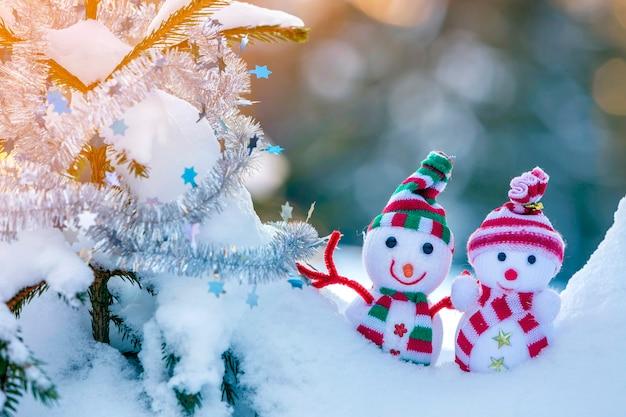 Dwa małe śmieszne zabawki bałwan dziecko w dzianych czapkach i szalikach w głębokim śniegu na zewnątrz w pobliżu gałęzi sosny. kartkę z życzeniami szczęśliwego nowego roku i wesołych świąt.