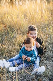 Dwa małego dziecko brata siedzi wpólnie w polu