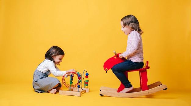 Dwa małej dziewczynki bawić się z zabawkami na żółtym odosobnionym tle