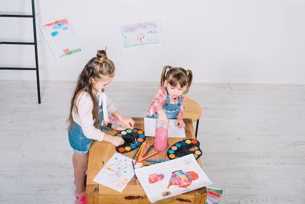 Dwa małej dziewczynki maluje z aquarelle przy drewnianym stołem