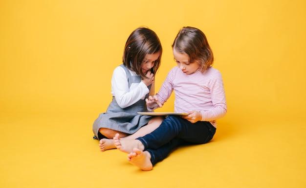 Dwa małej dziewczynki używa cyfrową pastylkę na żółtym tle