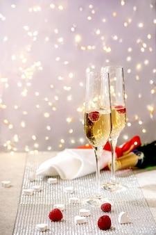 Dwa malinowe kieliszki do szampana na tacy stojącej na srebrnym musującym stole, białe serca, światła bokeh. świąteczne nakrycie stołu.