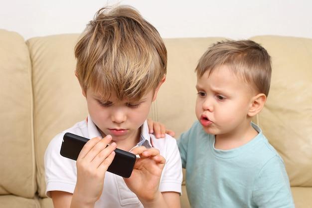 Dwa mały chłopiec spojrzeć na smartfona
