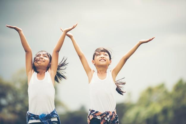 Dwa małych dziewczynek ręka trzyma up mieć zabawę plenerową
