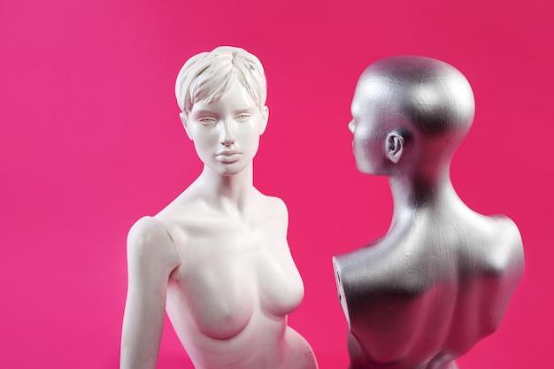 Dwa manekiny na różowej ścianie. moda i design.