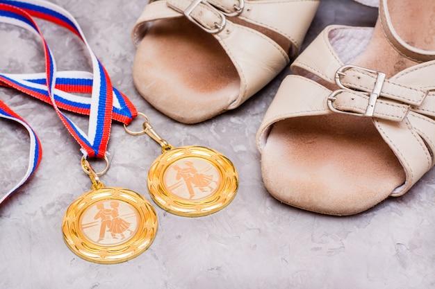 Dwa medale na wstążce i buty do tańca towarzyskiego
