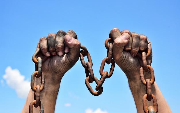 Dwa męskie ręce trzyma zardzewiały łańcuch metalowy