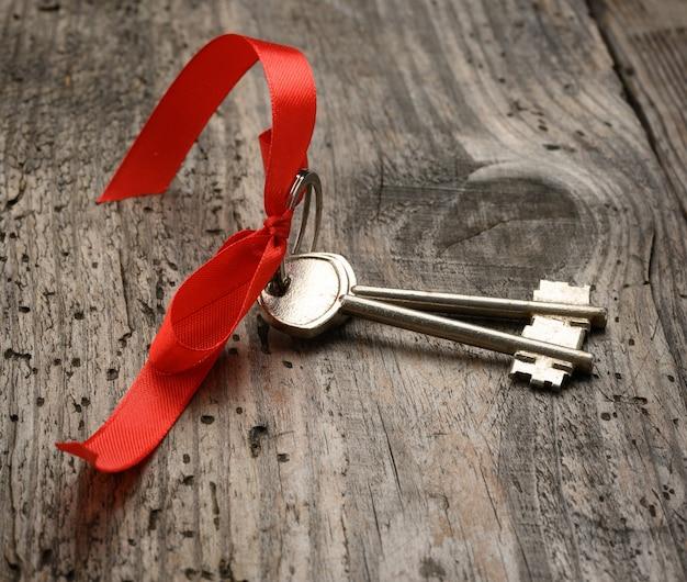 Dwa metalowe klucze do drzwi domu z czerwoną wstążką na drewnianym stole, koncepcja zakupu nieruchomości
