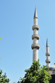 Dwa minarety na tle błękitnego nieba. minarety w stambule. zbliżenie minaretów w letni dzień.