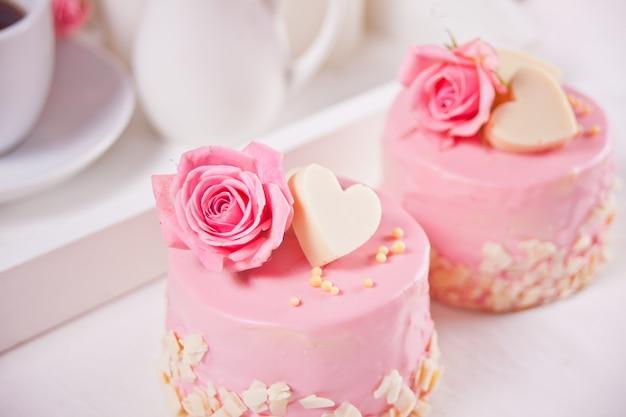 Dwa mini ciasta z różami na białym stole. koncepcja romantycznej kolacji