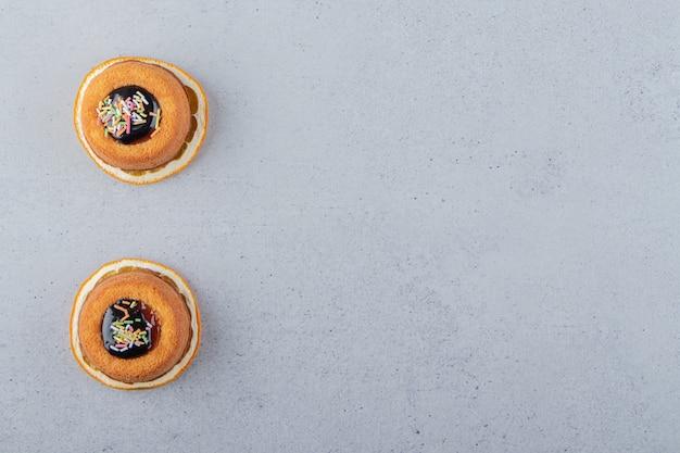 Dwa mini ciastka z galaretką ułożone na wierzchu plasterka pomarańczy. zdjęcie wysokiej jakości