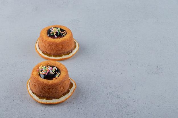 Dwa mini ciastka z galaretką ułożone na wierzchu plasterka pomarańczy