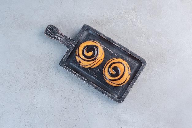 Dwa mini torty ozdobione polewą czekoladową na czarnej tablicy.