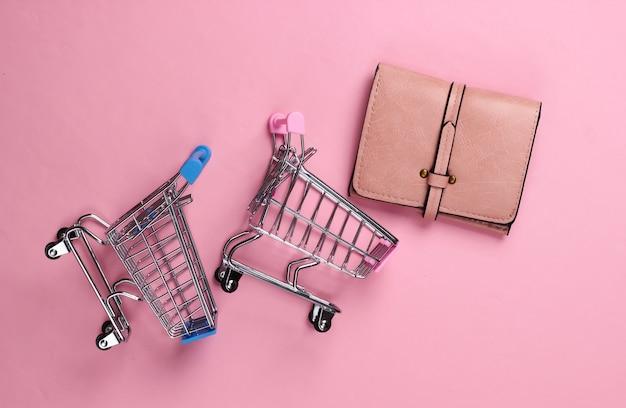 Dwa mini wózki supermarketowe z portfelem na różowym pastelowym kolorze