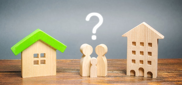 Dwa miniaturowe drewniane domy i rodzina pomiędzy nimi.