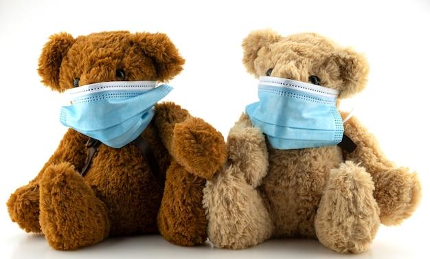 Dwa misie noszące maskę ochronną, pluszowy miś siedzi w niebieskich maskach medycznych na białym tle, koncepcja ochrony przed chorobami układu oddechowego, zatrzymanie koronawirusa i koncepcja zanieczyszczenia powietrza.