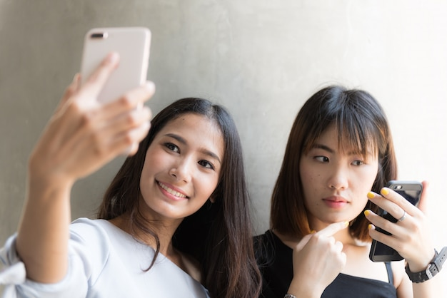 Dwa młoda azjatykcia dziewczyna używa telefon komórkowego ono selfie