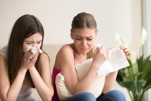 Dwa młoda kobieta przyjaciela płacze wpólnie w domu