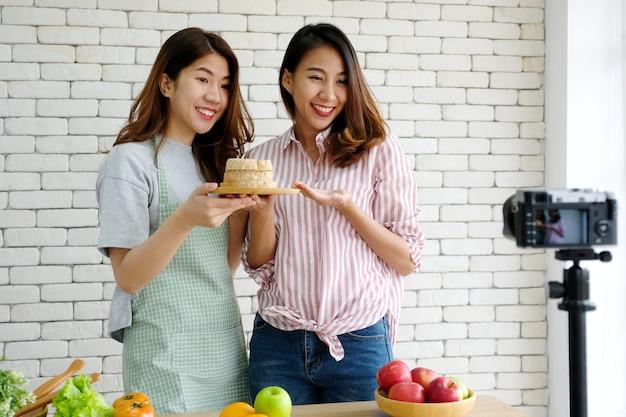 Dwa młodego azjatykciego kobiety jedzenia bloggers opowiada podczas gdy nagrywający wideo, vlog pojęcie