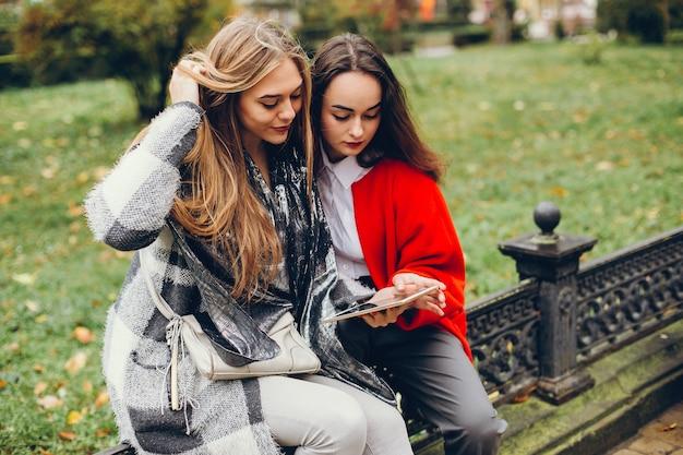Dwa młodego eleganckiego bizneswomanu siedzi w jesieni mieście i używają pastylkę
