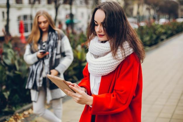 Dwa młodego eleganckiego bizneswomanu stoi w jesieni mieście i używają pastylkę