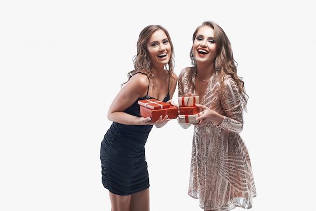 Dwa młodej dziewczyny z czerwonymi teraźniejszość w rękach odizolowywać na bielu