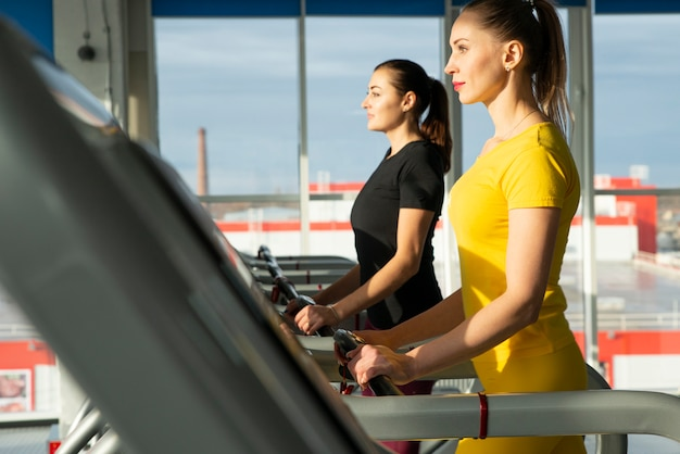 Dwa młodej kobiety biega na karuzeli w gym