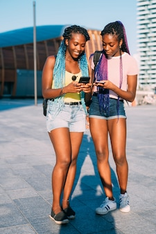 Dwa młodej pięknej czarnej siostry plenerowej używa smartphone
