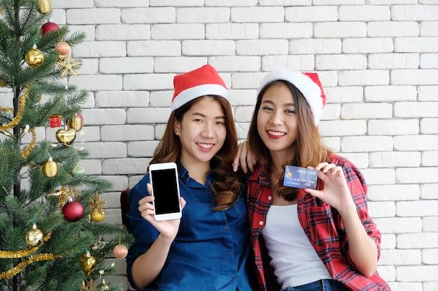 Dwa młodej ślicznej asia kobiety trzyma mądrze telefon z pustym ekranem i kredytową kartą dla shoppi