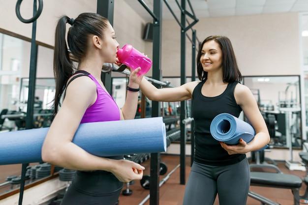 Dwa młodej uśmiechniętej sprawności fizycznej kobiety opowiada z sportem matują w gym
