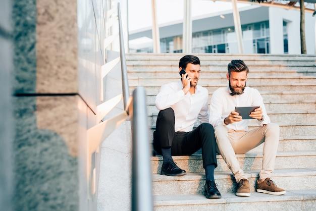 Dwa młody biznesmen używa technologicznych przyrząda