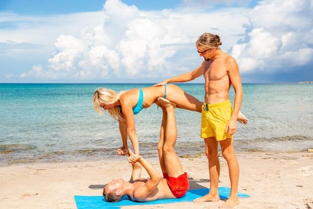 Dwa młody mężczyzna i kobieta na plaży robi joga fitness ćwiczenia razem. element acroyoga zapewniający siłę i równowagę