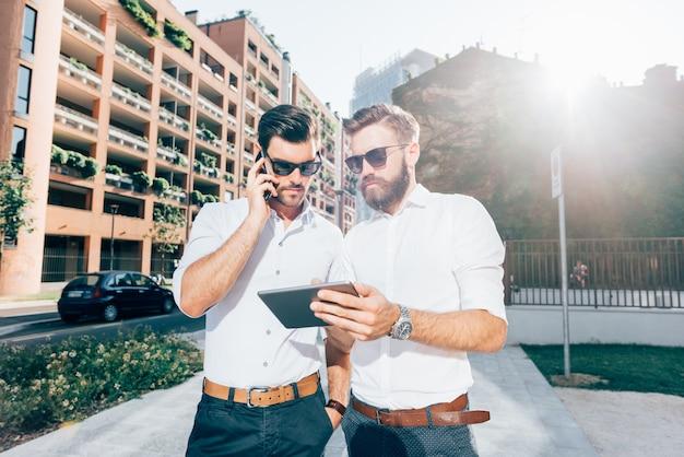 Dwa młody nowożytny biznesmen używa przyrząda