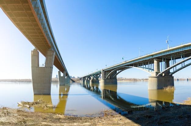 Dwa mosty na rzece, jedna kolejka metra i samochód.