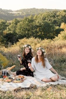 Dwa najlepszego przyjaciela na pikniku na polu kłaść na kłaść ono uśmiecha się