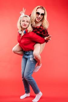 Dwa najlepszego żeńskiego przyjaciela pozuje wpólnie na czerwonym tle