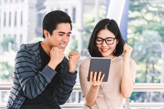 Dwa nastolatka ucznia robi pracie domowej z laptopem przy uniwersytetem